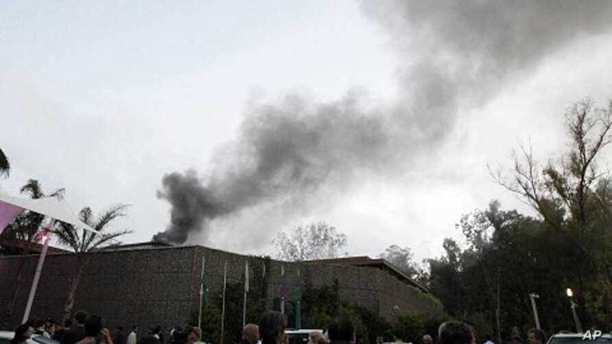 Foreign journalists gather outside of Rixos hotel as plume of smoke rises in the sky in Tripoli, Libya, June 9, 2011