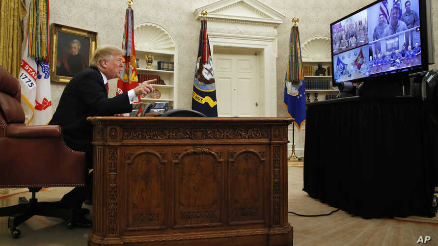 President Donald Trump greets members of the five branches of the military by video conference on Christmas Day, Dec. 25, 2018, in the Oval Office of the White House.