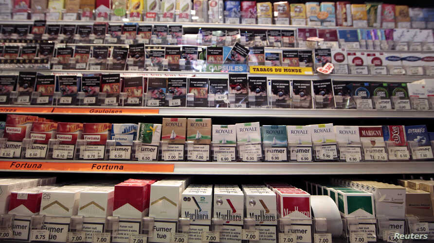 FILE - Cigarette packs are seen on shelves in a tobacco shop in Cagnes-sur-Mer, France, Sept. 8, 2015. The World Health Organization on Tuesday called on countries do adopt plain packaging to make tobacco products less attractive and reduce deaths fr
