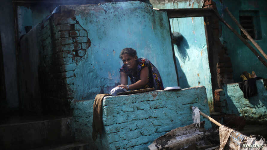 FILE - A woman cooks food outside her partially damaged house at the cyclone-hit Gopalpur village, in Ganjam district in the eastern Indian state of Odisha Oct. 14, 2013.