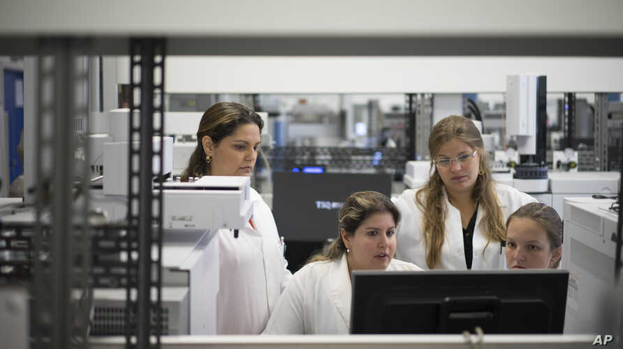 FILE - Lab technicians work at the Brazilian Doping Control Laboratory (LBCD) before a visit by Brazil's sports minister in Rio de Janeiro, Brazil, Friday, May 8, 2015.
