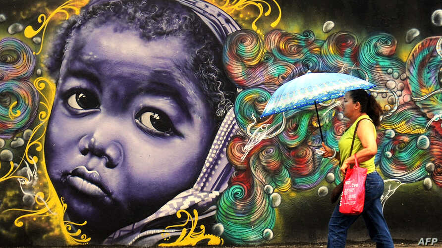 A woman passes by a graffiti in Salvador da Bahia, Brazil, June 18, 2013.