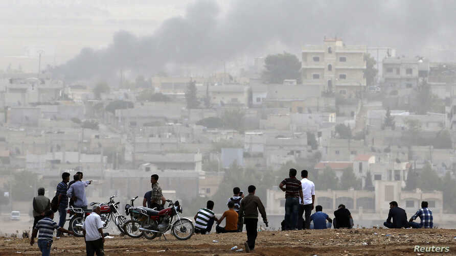 Turkish Kurds watch over Syrian town of Kobani from hill near Mursitpinar border crossing, southeastern Turkey, Oct. 11, 2014.