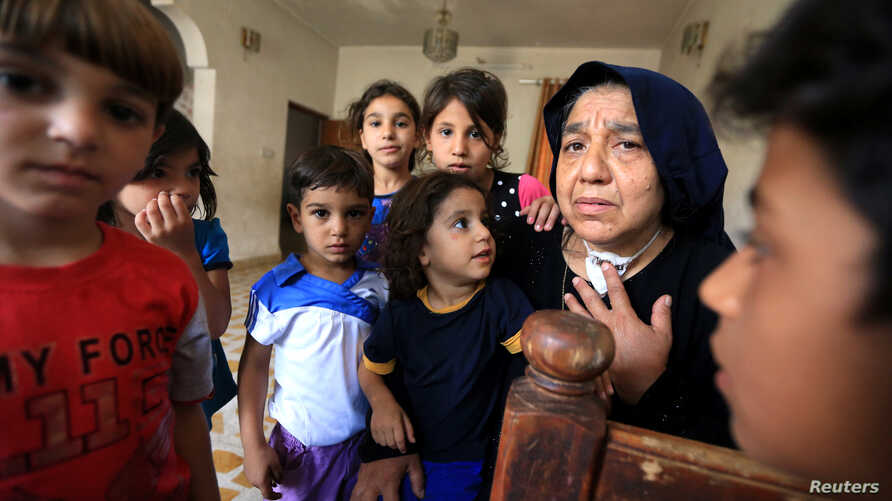 FILE - Sana Ibrahim al-Taee, 64, whose five sons were killed by Islamic State militants, is seen with her grandchildren at her home in Mosul, Iraq, July 30, 2018.