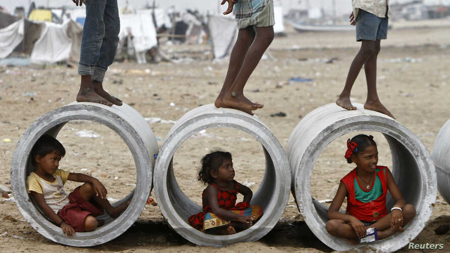 FILE - Children sitting inside cement water pipes play on the Marina beach in the southern Indian city of Chennai October 10, 2013.
