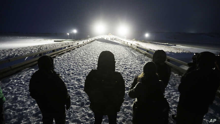 Military veterans stand on a bridge across from police protecting the Dakota Access oil pipeline site in Cannon Ball, N.D., Dec. 1, 2016.