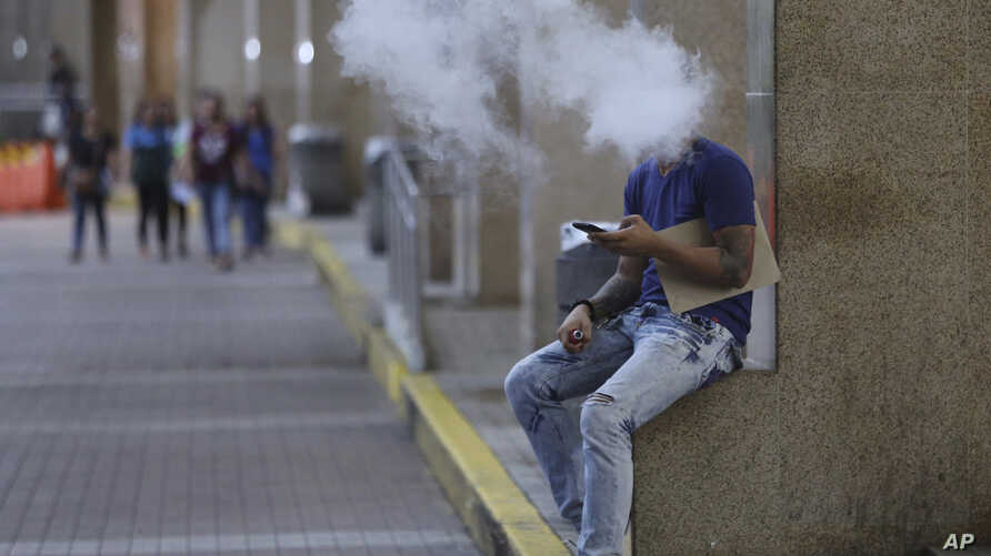 Philippines Public Smoking Ban: A Filipino uses an electronic cigarette outside a mall in Manila, Philippines Tuesday, Oct. 11, 2016.