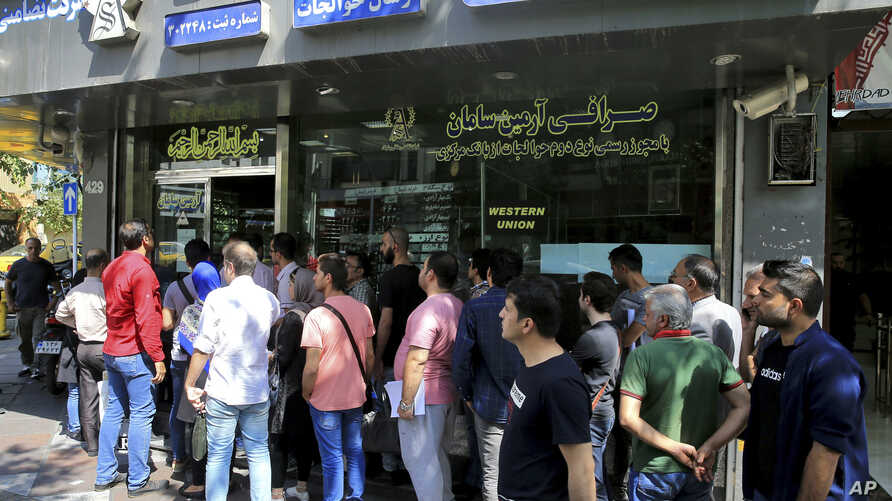 People line up in front of a currency exchange shop to buy U.S. dollars and euros, in downtown Tehran, Iran, Sept. 5, 2018. The Iranian rial fell Wednesday to its lowest rate on record and saw worried residents of Tehran line up outside of beleaguere