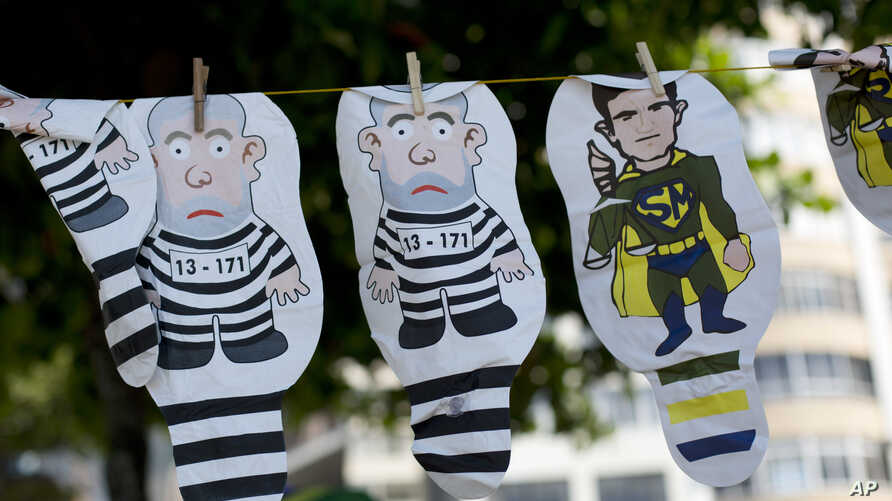 FILE - A set of inflatable dolls in the likeness of former President Luis Inacio Lula da Silva in prison garb and Judge Sergio Moro as a superhero hang on a line for sale during a protest against corruption and in support of the Car Wash investigatio