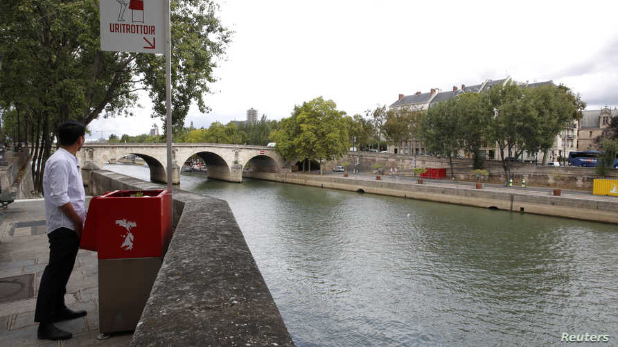 A journalist poses in front of a bright red, eco-friendly urinal on the Ile Saint-Louis along the Seine River in Paris, France, Aug. 13, 2018.