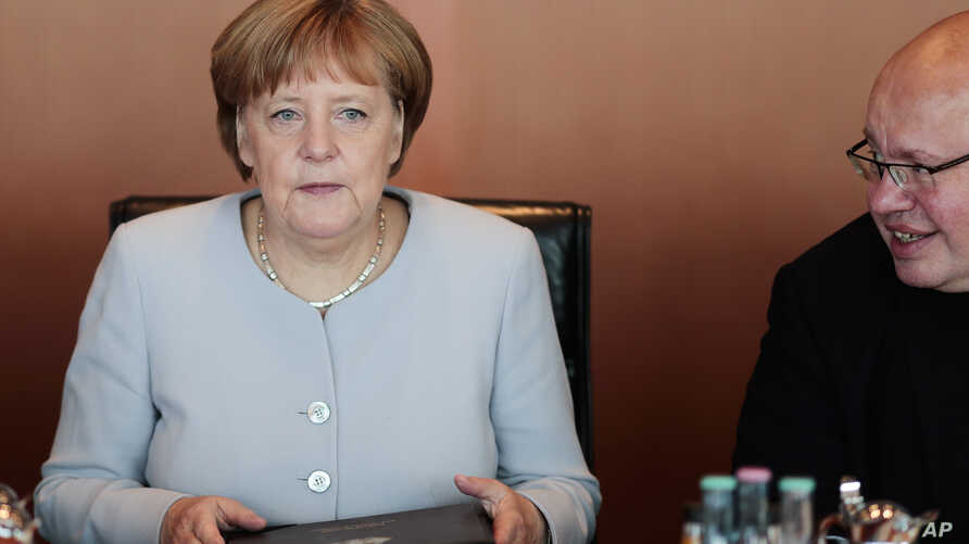 German Chancellor Angela Merkel, left, listens to chief of staff Peter Altmaier during a cabinet meeting at the chancellery in Berlin, July 6, 2016.