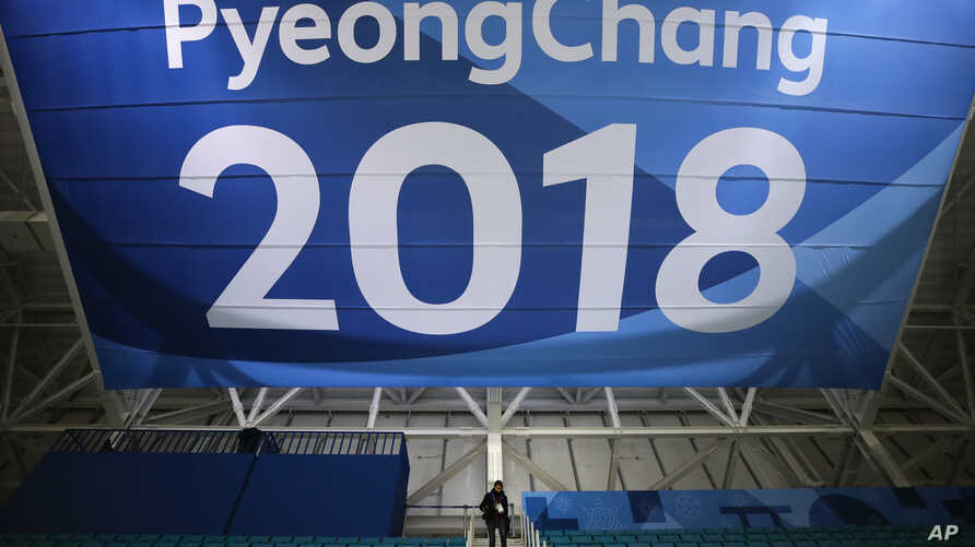 FILE - In this Feb. 6, 2018 file photo, a photographer walks down the steps underneath a large banner at the Gangneung Hockey Center ahead of the 2018 Winter Olympics in Gangneung, South Korea.