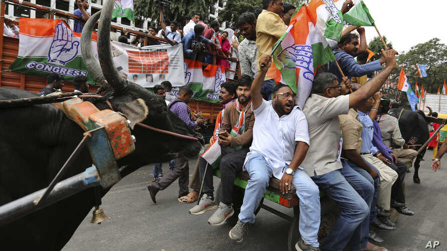Congress party supporters shout slogans as they ride on bullock carts during a protest against fuel price hike and other economy issues in Bangalore, India, Sept. 10, 2018.