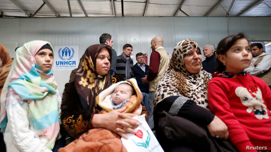 Syrian refugees wait to receive treatment at a health center, during the visit of Slovenian President Borut Pahor (back C) to the refugee camp Al Zaatari in Jordan, near the border with Syria, Dec. 3, 2016.