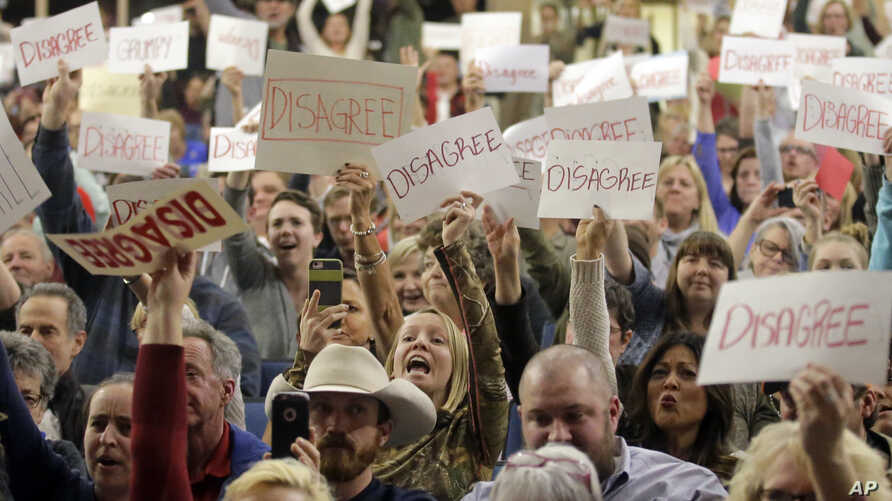 People react to Rep. Jason Chaffetz as he speaks during a town hall meeting, Feb. 9, 2017, in Cottonwood Heights, Utah. Hundreds of people lined up early for the town hall with Chaffetz, many holding signs criticizing the congressman's push to repea