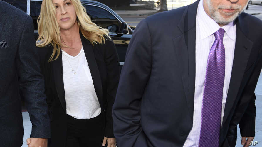 Singer Alanis Morissette, left, arrives with attorney Allen Grodsky at U.S. federal court for the sentencing in the embezzlement case of her former manager Jonathan Todd Schwartz, May 3, 2017, in Los Angeles.