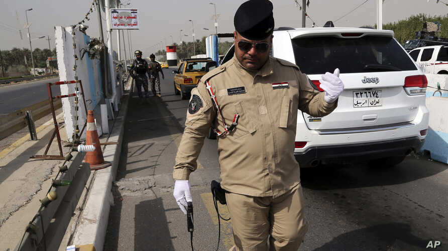 An Iraqi federal policeman uses a device meant to detect bombs at a checkpoint in Baghdad, Iraq, Oct. 11, 2014.