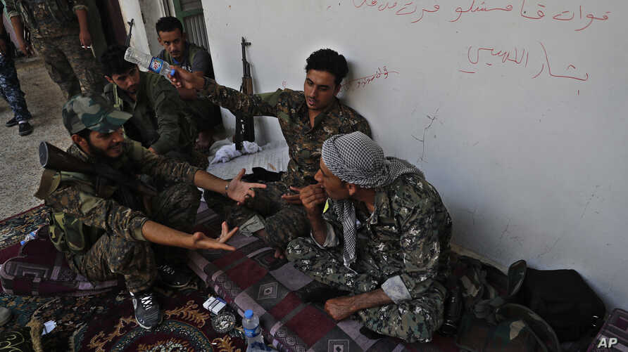 U.S.-backed Syrian Democratic Forces fighters talk to each other at their position where they were battling Islamic State militants, on the front line on the western side of Raqqa, northeast Syria, July 17, 2017.