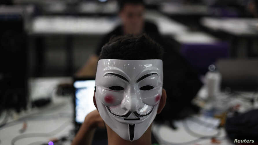 """A man wearing a Guy Fawkes mask surfs the web during a """"Campus Party"""" Internet users gathering in Sao Paulo, January 30, 2013."""
