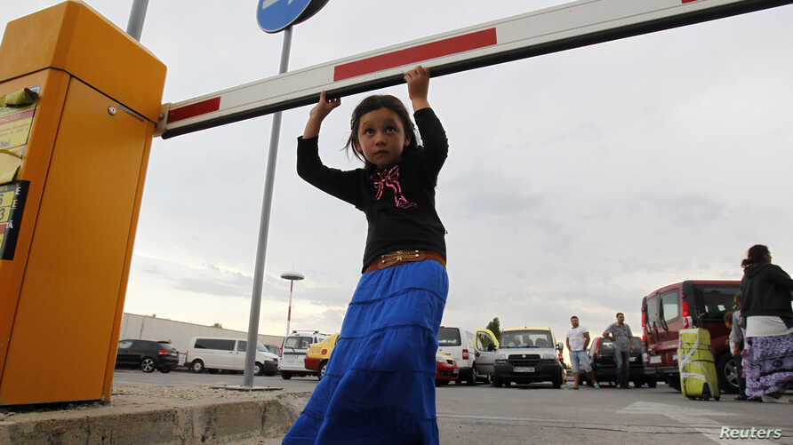 A member of Romania's ethnic Roma minority arrives at Bucharest airport, Aug. 9, 2012.