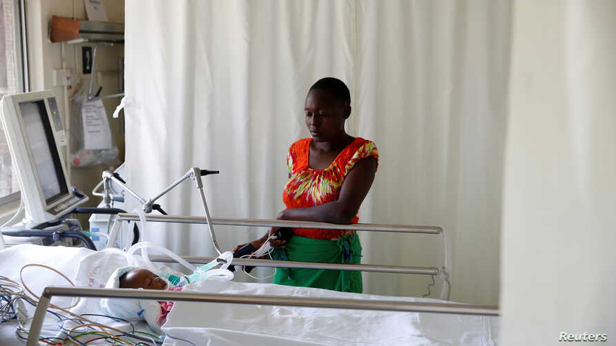 FILE - Lenzer, mother of six month-old Samantha Pendo, stands next to her bed as the girl remains in critical condition in the Intensive Care Unit of Aga Khan Hospital in Kisumu, Kenya August 14, 2017.