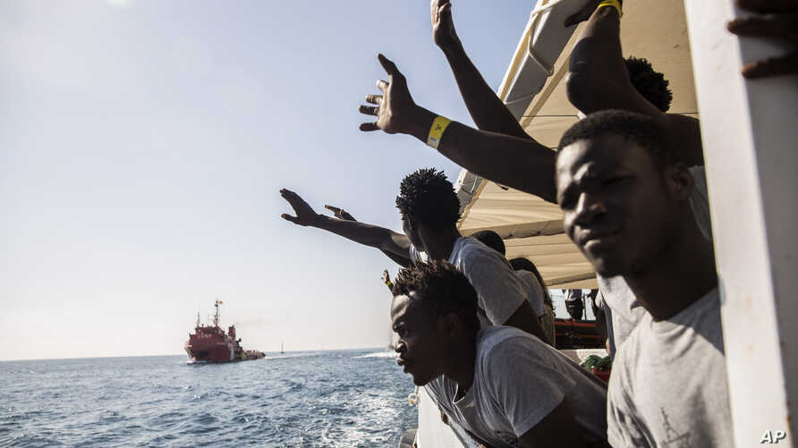 Migrants aboard the Open Arms aid boat, of Proactiva Open Arms Spanish NGO, react as the ship approaches the port of Barcelona, Spain, Wednesday, July 4, 2018. The aid boat sailed to Spain with 60 migrants rescued on Saturday in waters near Libya, af...