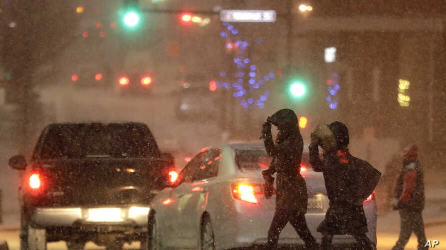 Pedestrians walk across a snowy street in downtown Kansas City, Mo., Dec. 17, 2016. A winter storm of snow, freezing rain and bone-chilling temperatures hit the nation's midsection and East Coast on Saturday.
