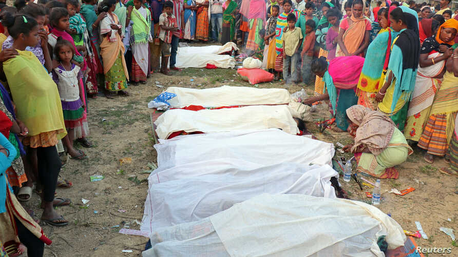 rePeople stand next to the bodies of tea plantation workers, who died after consuming bootleg liquor, in Golaghat in the northeastern state of Assam, India, Feb. 22, 2019.