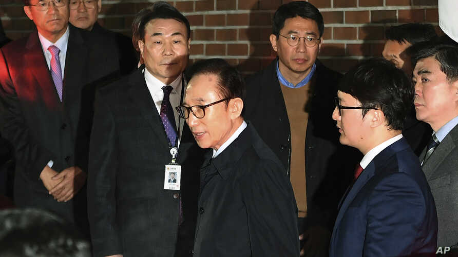 Former South Korean President Lee Myung-bak, centre,  gets into a car as he is transferred to a detention centre, at his residence in Seoul early Friday  March 23, 2018.