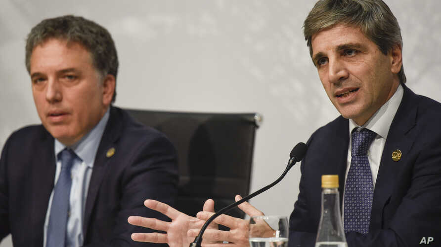 FILE - Argentine Central Bank President Luis Caputo speaks as Argentine Treasury Minister Nicolas Dujovne looks on during a press conference at the G20 meeting of Finance Ministers and Central Bank governors in Buenos Aires, Argentina, July 22, 2018.