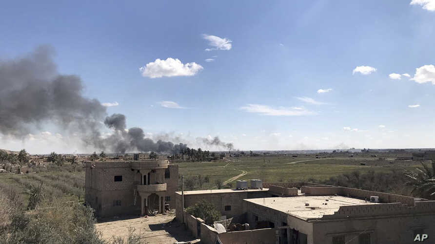 Columns of black smoke rise from the last small piece of territory held by Islamic State militants as U.S. backed fighters pound the area with artillery fire and occasional airstrikes, as seen from outside Baghouz, Syria, March 3, 2019.