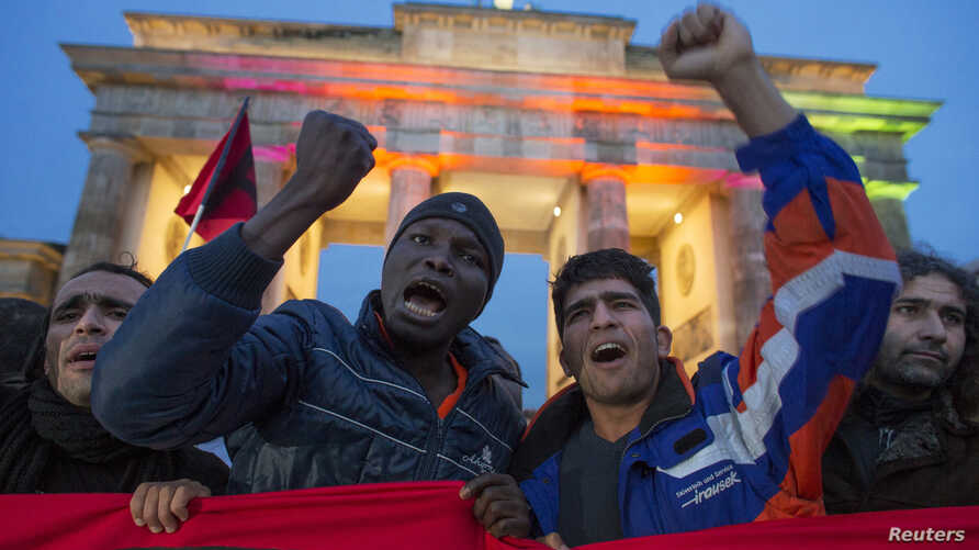 Refugees shout slogans during a protest by asylum seekers calling for fairer treatment from authorities, as they pass through Brandenburg Gate in Berlin, October 13, 2012.