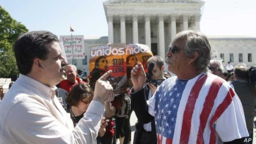 Mark Jenkins (L), an opponent of Arizona Senate Bill 1070 and Blake Sutherland (R), a supporter of the bill, discuss their opposite viewpoints outside the U.S. Supreme Court in Washington, April 25, 2012.