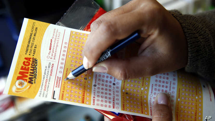 A customer picks numbers for a Mega Millions lottery ticket at a convenience store in Chicago, July 1, 2016.