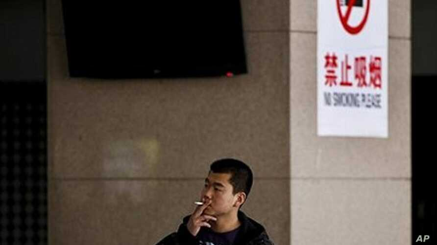 A Chinese man smokes in front of a pillar with a no smoking notice on display at a bus station in Beijing, March 24, 2011