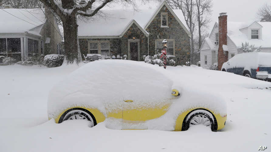 A snow-covered car is parked outside a home in Greensboro, North Carolina, Dec. 9, 2018. A massive storm brought snow, sleet, and freezing rain across a wide swath of the South on Sunday.