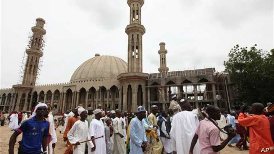 In this photo taken Thursday, Aug. 8, 2013, Nigerian Muslims walk past an uncompleted mosque in Maiduguri, Nigeria. Suspected Islamic militants wearing army fatigues gunned down 44 people praying at a mosque in northeast Nigeria, while another 12 civ