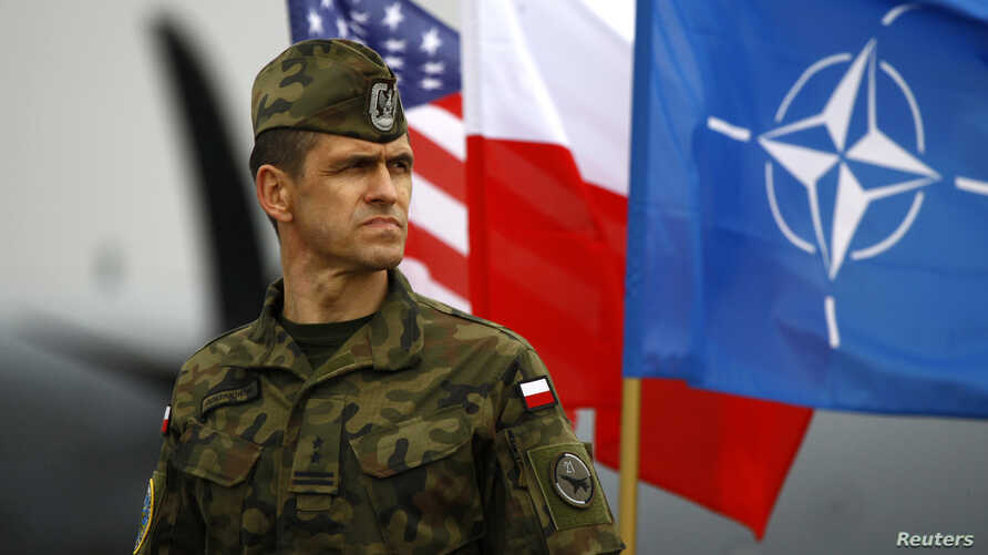FILE - A Polish soldier stands in front of U.S., Polish and NATO flags ahead of military exercises in Swidwin, northwestern Poland, April 23, 2014.