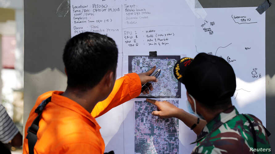 Rescue team members point to a map as they try to recover dead bodies after an earthquake hit Petobo neighborhood in Palu, Indonesia, Oct. 5, 2018.