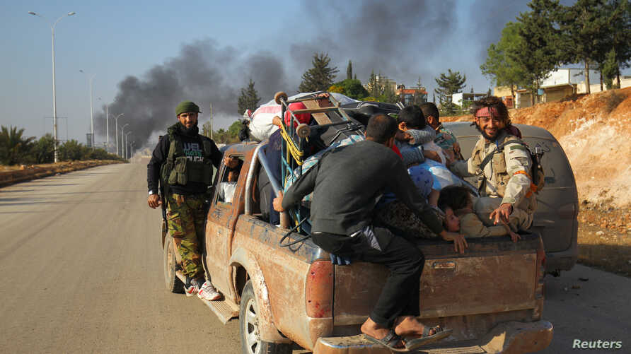 Rebel fighters ride a pick-up truck with civilians who fled areas of conflict in Dahiyet al-Assad, west Aleppo city, Syria, Oct. 30, 2016.