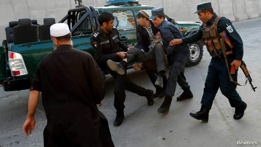 Afghan policemen carry an injured man after a blast in Kabul, Oct. 31, 2017.