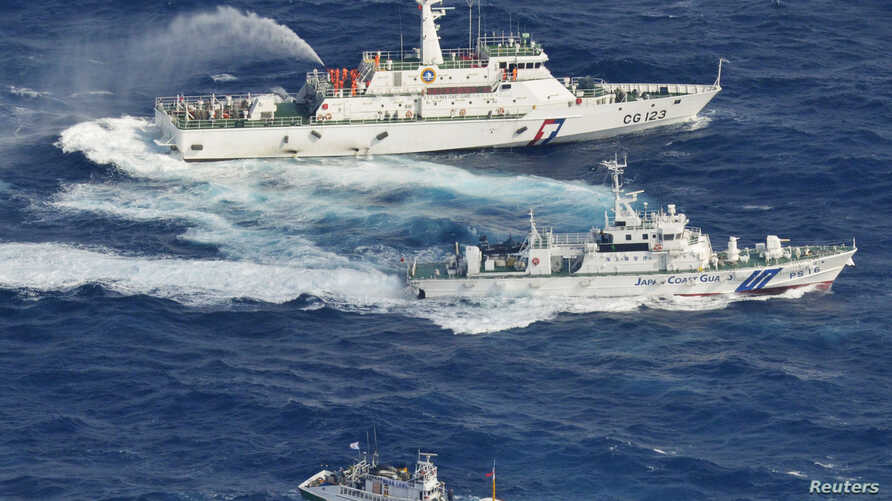 An aerial view shows a Japan Coast Guard patrol ship (C) spraying water at a fishing boat from Taiwan as Taiwan's Coast Guard vessel (top) sprays water near the disputed islands in the East China Sea, September 25, 2012.