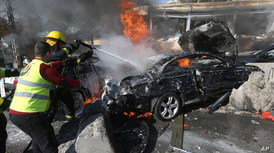 Lebanese firefighters extinguish a burning car at the site of an explosion near the Kuwaiti Embassy and Iran's cultural center, in the suburb of Beir Hassan, Beirut, Lebanon, Wednesday, Feb. 19, 2014. The bombing in a Shiite district in southern Beir