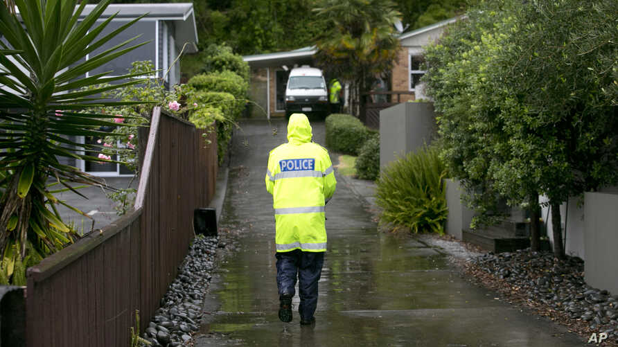 A police officer walks to a house to advise residents to evacuate as fears grow about possible storm surges at high tide in Ohope, New Zealand.