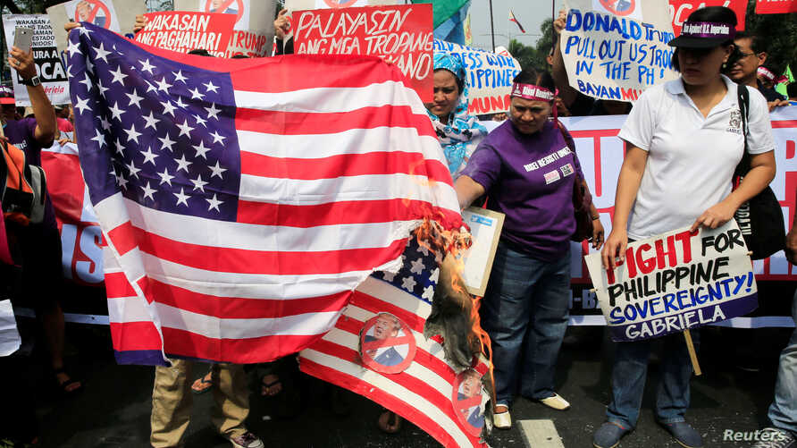 Protesters burn a U.S. flag and a mock flag with pictures of U.S. President-elect Donald Trump outside the U.S. embassy in metro Manila, Philippines, Jan. 20, 2017.