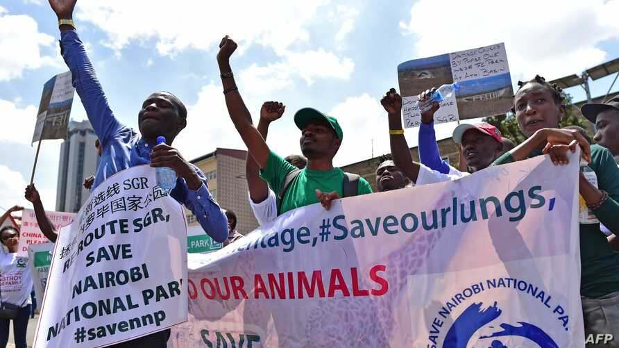 Environmental activists chant slogans as they carry placards and banners during a protest in Nairobi, Kenya, March 1, 2018, against a government decision to construct a standard-gauge railway line across the Nairobi National Park.
