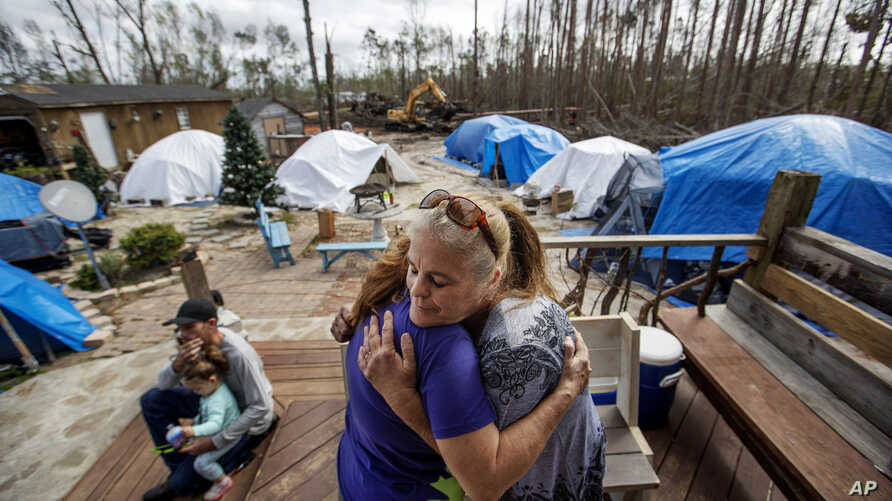 "Diahnn ""Shelly"" Summers, right, embraces Lori Hogan, who is currently living in a tent in Summers' backyard months after Hurricane Michael hit in Youngstown, Fla, Wednesday, Jan. 23, 2019."