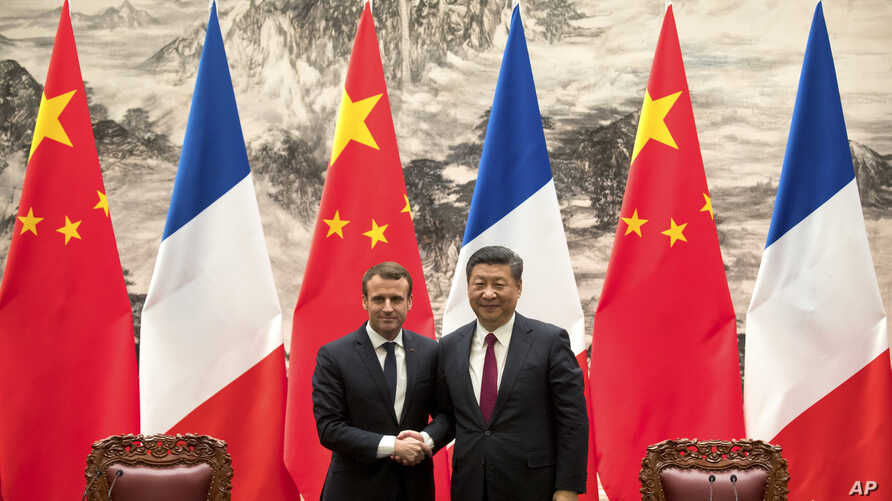 French President Emmanuel Macron, left, and Chinese President Xi Jinping shake hands after a joint press briefing at the Great Hall of the People in Beijing, Tuesday, Jan. 9, 2018.