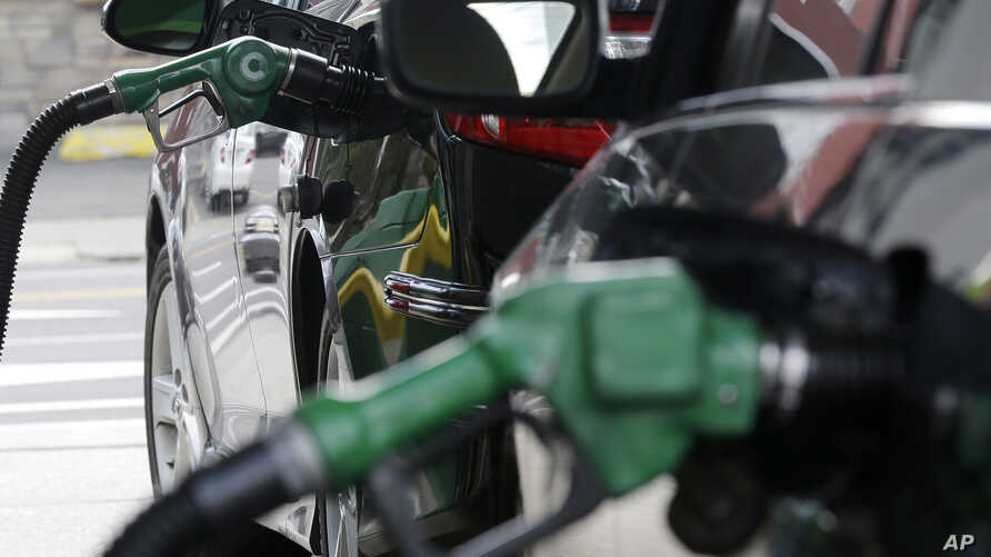 FILE - Gas is pumped into vehicles at a BP gas station in Hoboken, N.J., June 30, 2016. Federal regulators will review strict vehicle fuel efficiency standards finalized days before President Donald Trump took office.