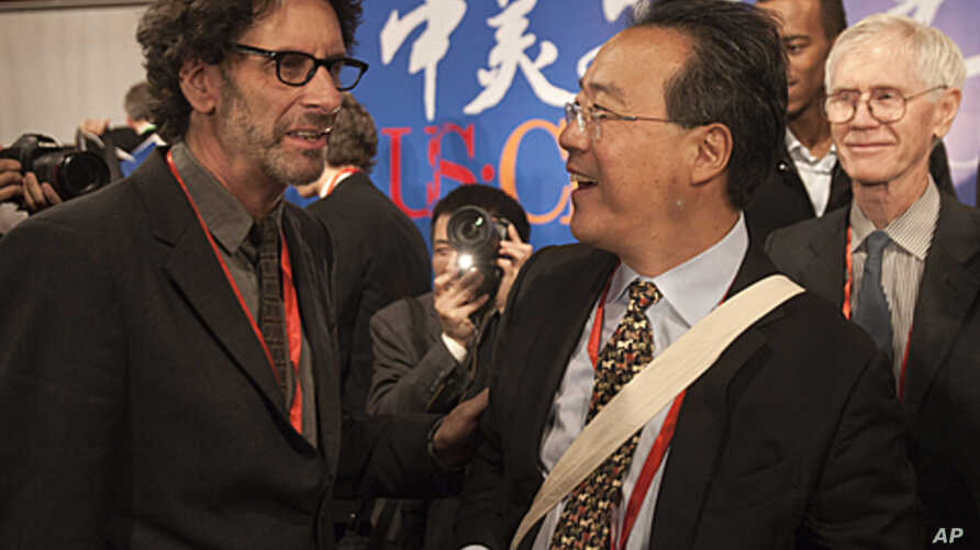 """American film director Joel Coen, left, chats with French-born American cellist Ma Yo-Yo after the opening of a forum on """"the U.S.-China arts and culture"""" at National Center for the Performing Arts in Beijing, China, November 17, 2011."""